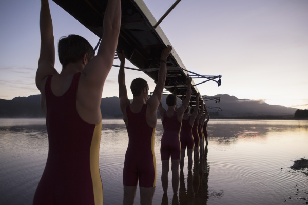 rowing team carrying boat overhead into