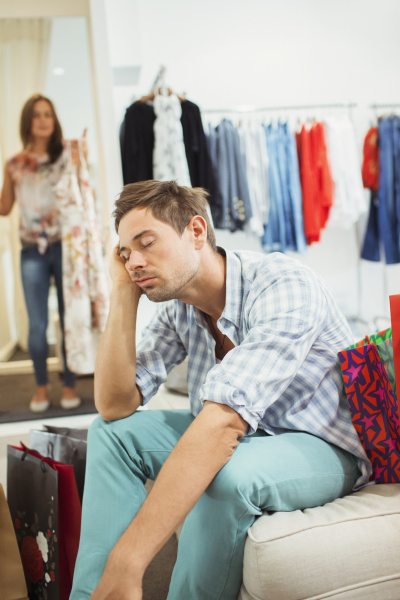 bored man shopping with girlfriend in