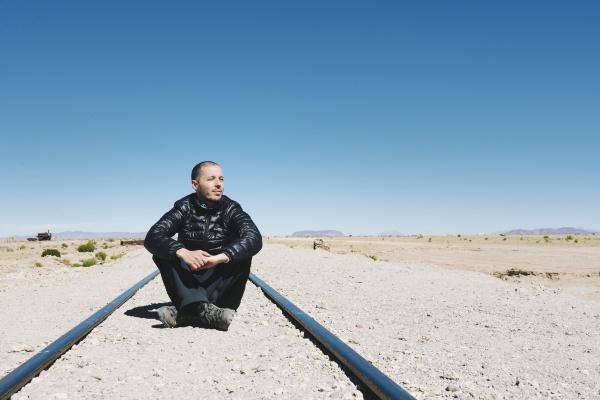 bolivia uyuni train cemetery man sitting