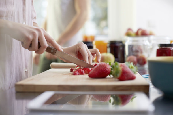 woman cutting strawberries in kitchen