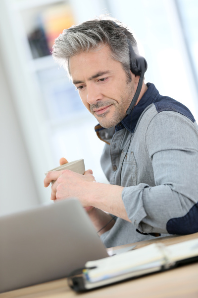 mature man teleworking from home with