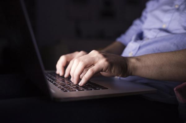 man working at night using laptop