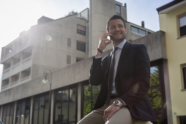 smiling businessman outdoors on cell phone