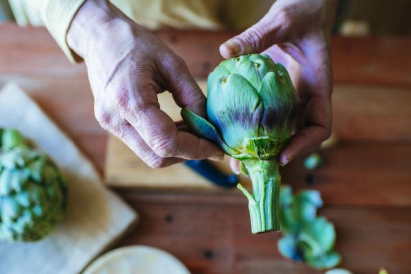 womans hands peeling an artichoke close