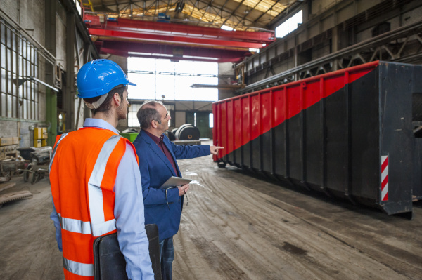 manager and worker talking at container