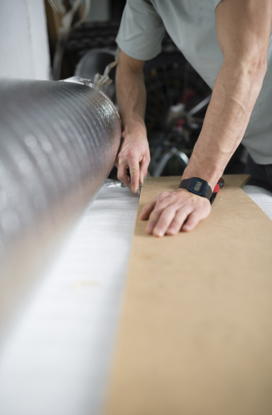 young man cutting a insulating material