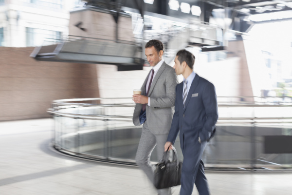 corporate businessmen with coffee walking and