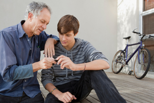 father and son examining tool together