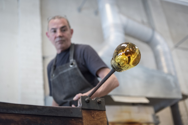 glassblower with large blob of hot