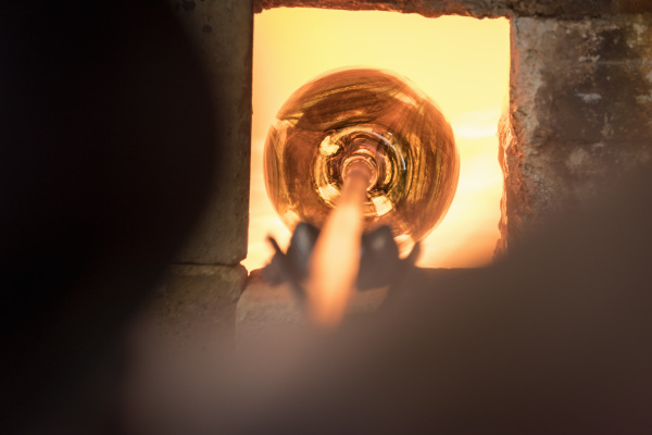 glassblower heating glass in furnace