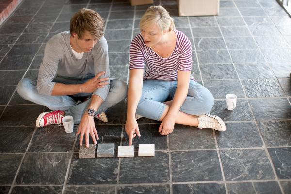 young couple sitting on floor choosing