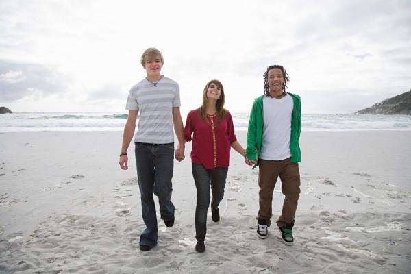 three people walking on beach holding