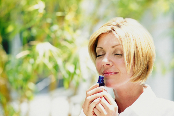 woman smelling scent outdoors
