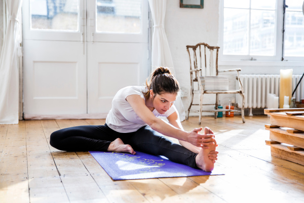 young woman practicing yoga touching toes