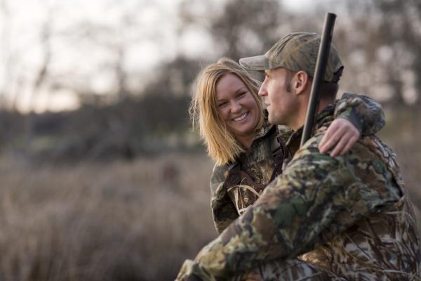 happy couple wearing camouflage clothing