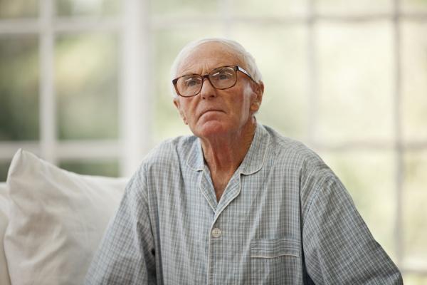 concerned senior man wearing pajamas inside
