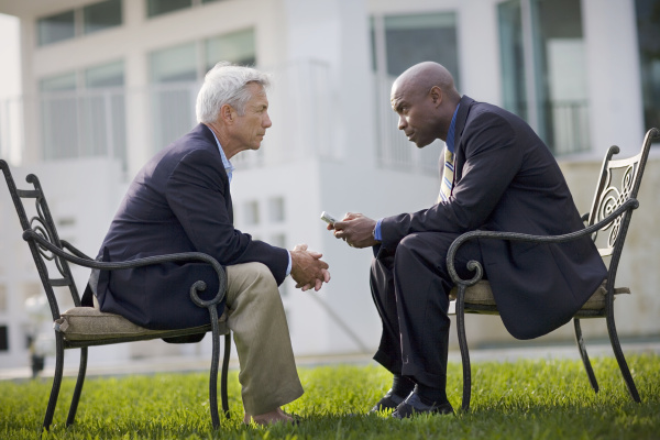 two businessmen having a discussion outside