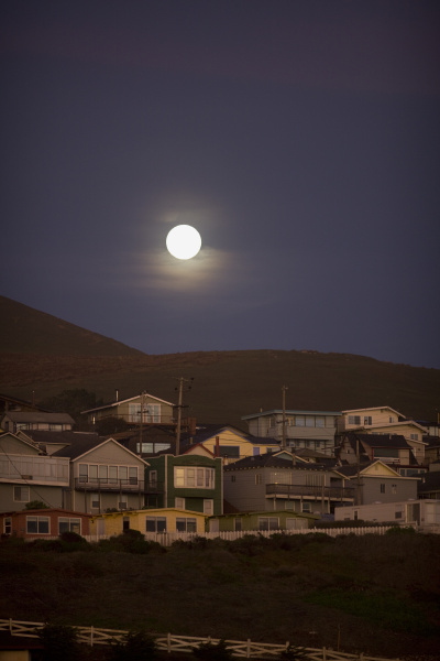 full moon rising above a small