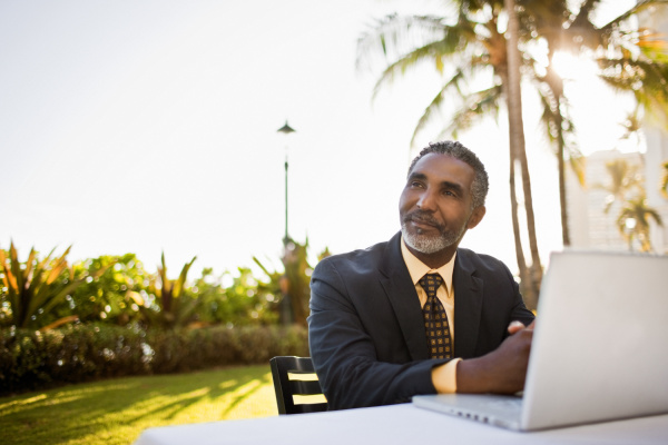 businessman sitting at table outside using