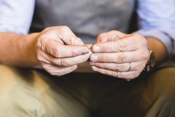 hands of a mature cobbler close