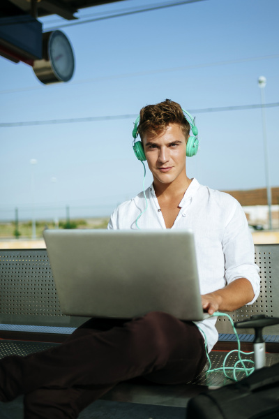 young man wearing headphones and using