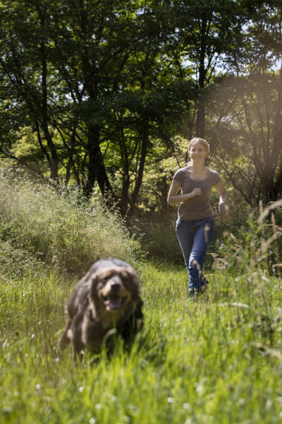 young woman running after her dog