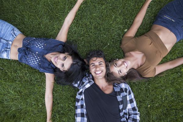 three happy friends lying on meadow