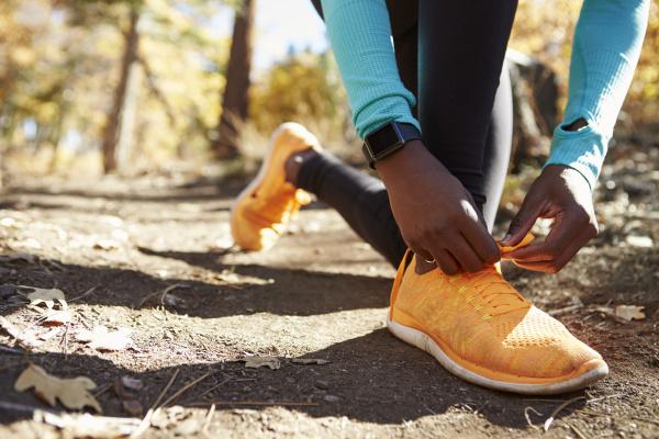 black female runner in forest tying