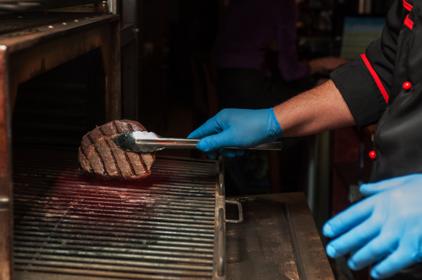 chef roasts meat steak