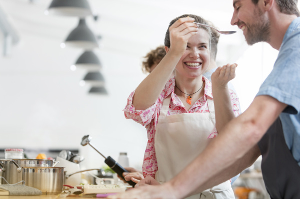 smiling couple tasting food in cooking