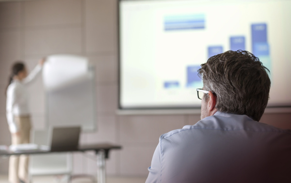 businessman watching businesswoman leading meeting at