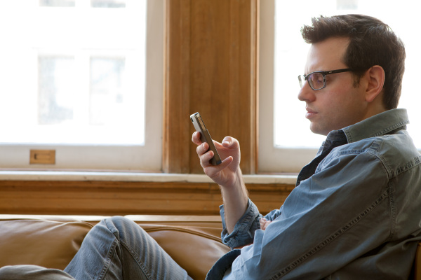 mid adult man using smartphone side