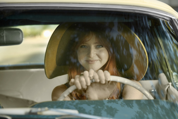 portrait of young woman driving vintage