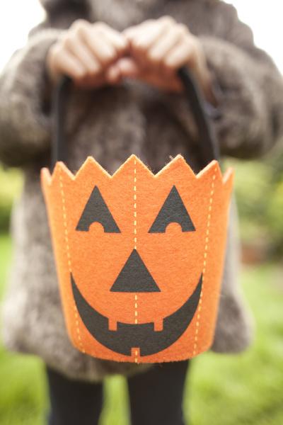 girl holding up halloween pumpkin bag