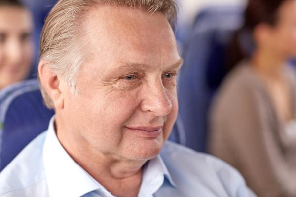 happy senior man sitting in travel