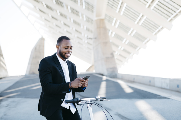 smiling businessman on bicycle looking at