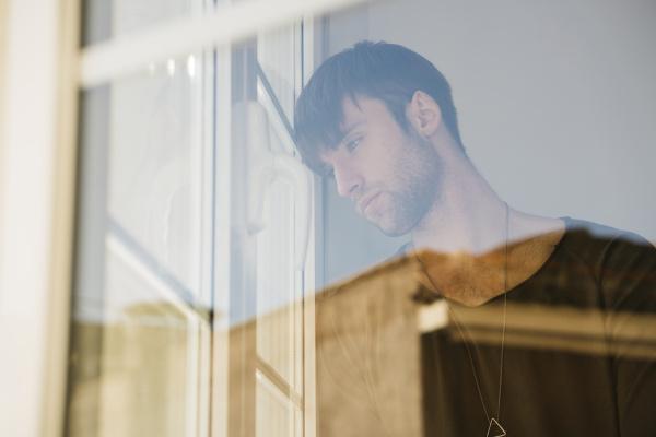 sad young man looking through window