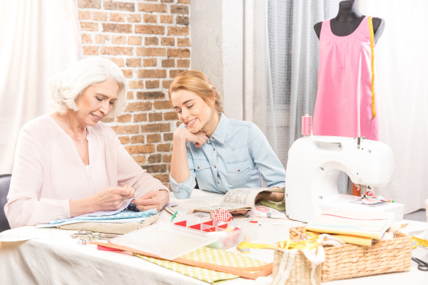 senior woman and girl sewing