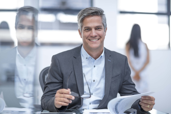 businessman holding spectacles reading documents
