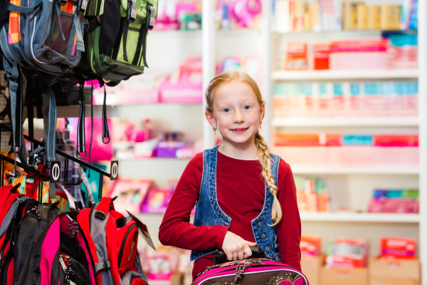 child choosing school satchel in store