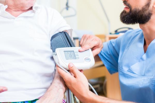 nurse measuring blood pressure of senior