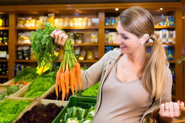 pregnant woman buying healthy vegetables in