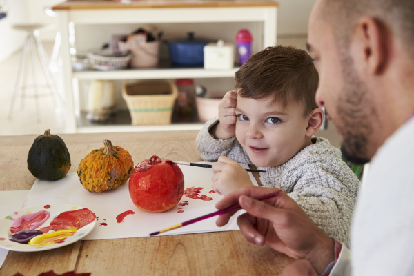 father and son decorating halloween pumpkins