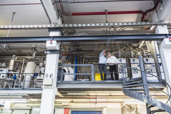 two men talking in factory shop