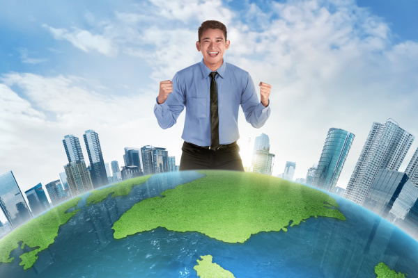 happy asian businessman standing behind earth