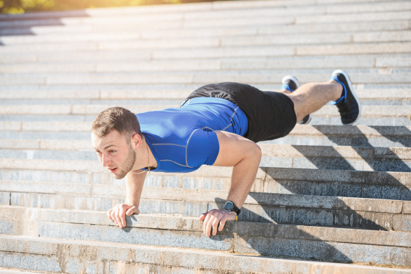 fit man doing exercises outdoors at