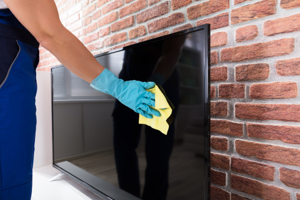 person cleaning the television screen with