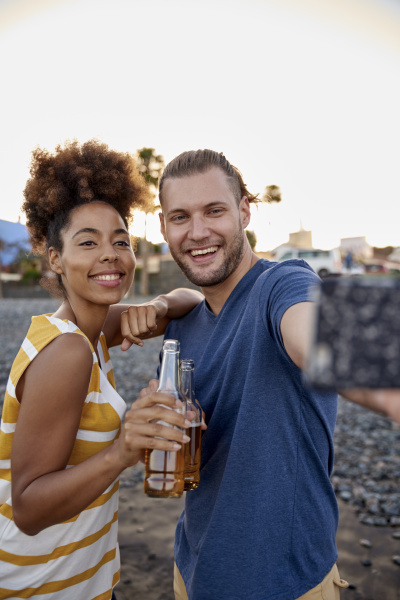 two friends with beer bottles taking