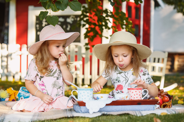 two little girls sitting on green