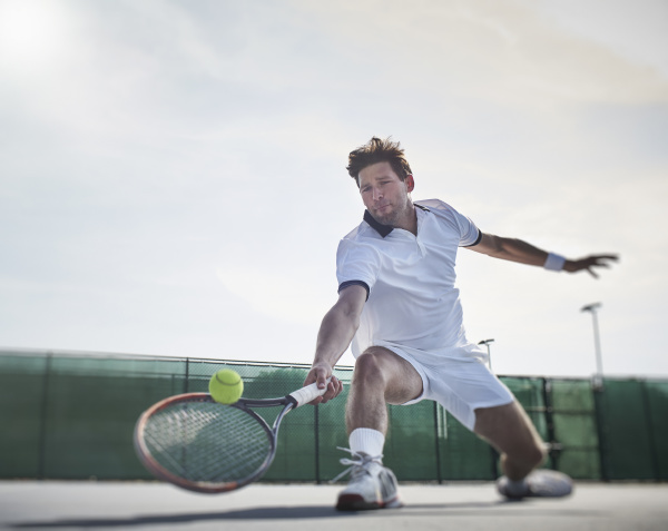 determined young male tennis player playing